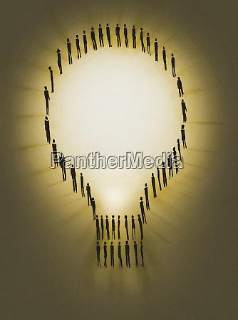 people outlining illuminated light bulb