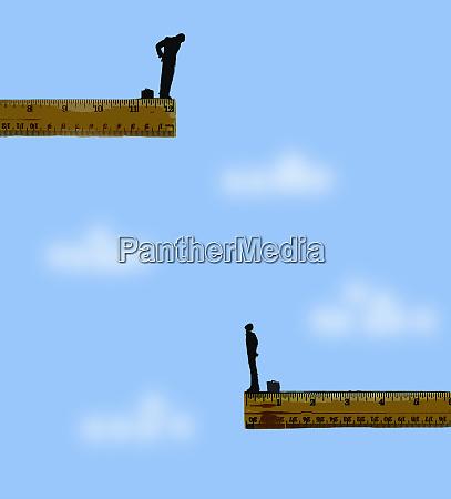 gap between businessmen on rulers in