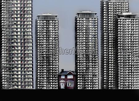 kleines einfamilienhaus umgeben von hohen wohnbloecken