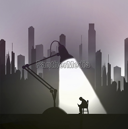 man sitting under spotlight texting