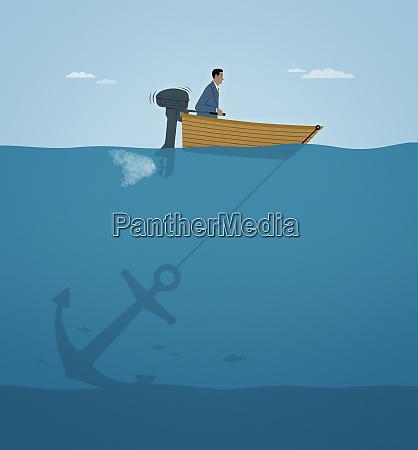 businessman stuck in motorboat oblivious of
