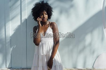 young woman wearing white dress talking