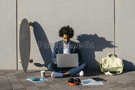 ung forretningsmand sidder udendors ved en
