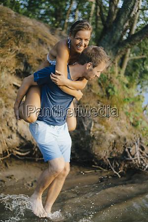 happy man carrying girlfriend piggyback at