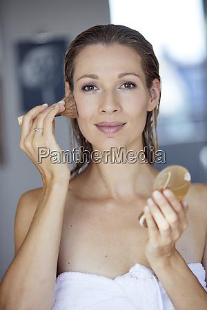 portraet af blond kvinde anvender makeup