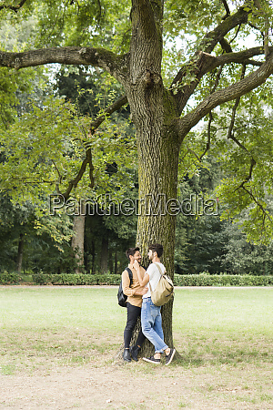 happy young gay couple leaning against