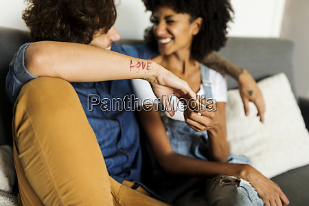 happy couple sitting on couch talking