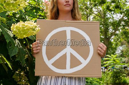 kvinde holder fred symbol af traeer