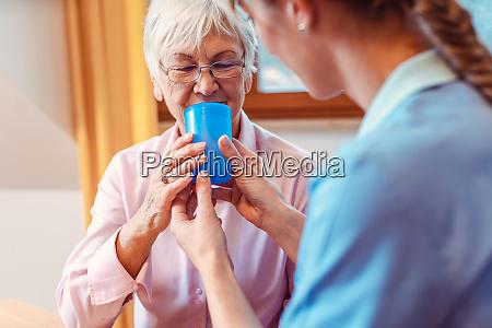omsorgsperson hjaelper senior kvinde drikker give
