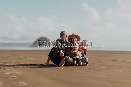 parents and children sitting on beach