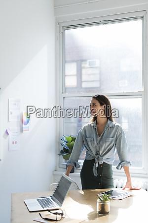 business kvinde staende bag kontor desk