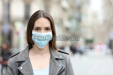 kvinde med beskyttende maske kigger pa