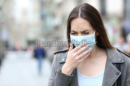 syg kvinde med beskyttende maske hoste