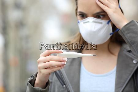 bekymret pige med maske kontrol termometer