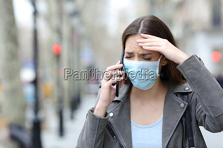 bekymret kvinde med beskyttende maske ringer