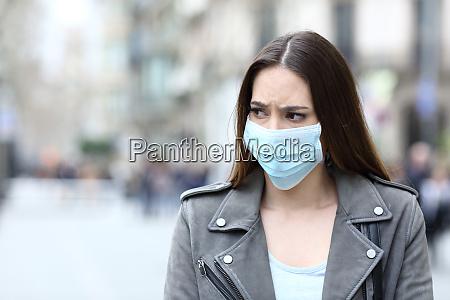 bange kvinde med beskyttende maske undga