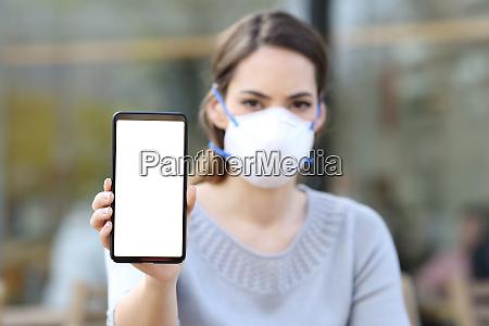kvinde med maske viser telefon med