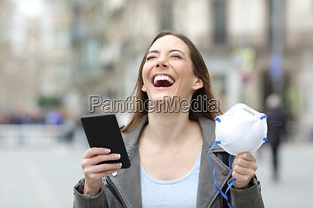 spaendt kvinde holder telefon og maske
