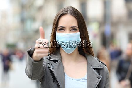 glad kvinde med maske gestikulerende tommelfingre