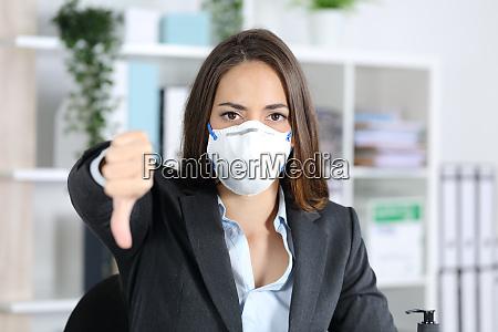 executive med maske gestikulerer tommelfingre ned