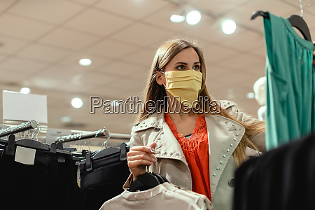 kvinde shopping i modebutik ifort ansigtsmaske