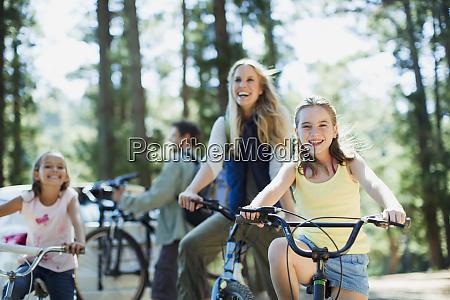 smilende familie cykelture i skoven