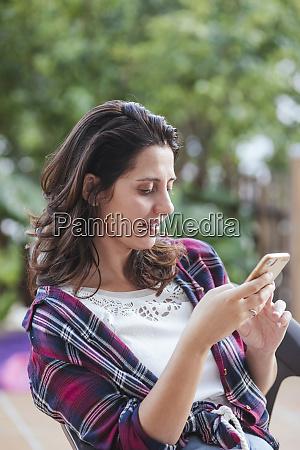 kvinde bruger smartphone i haven