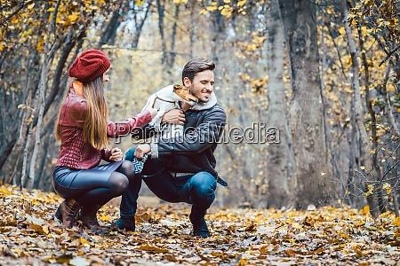 kvinde og mand klapper hunden ga