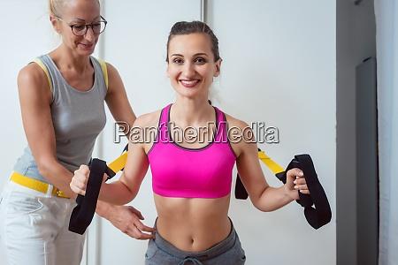 kvinde bruger slynge traener under fysioterapi