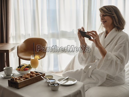 smilende blond aeldre kvinde fotografere morgenmad