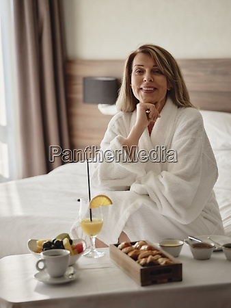 smilende afslappet blond kvinde sidder med