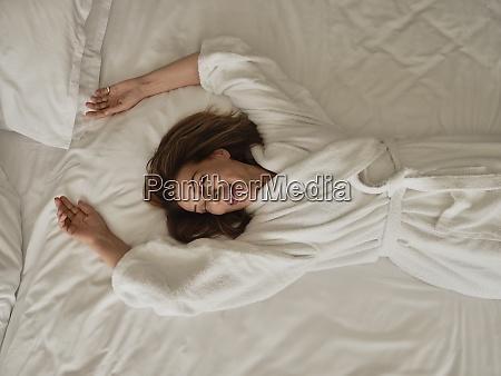 smilende seniorkvinde liggende pa hvid seng