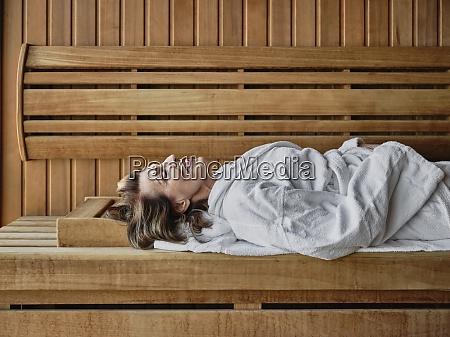 senior kvinde liggende pa trae sauna