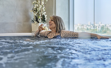 glad kvinde drikker i swimmingpool pa